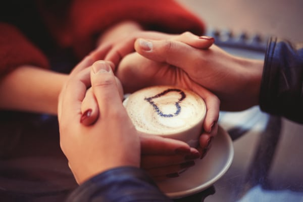 holding hands over coffee
