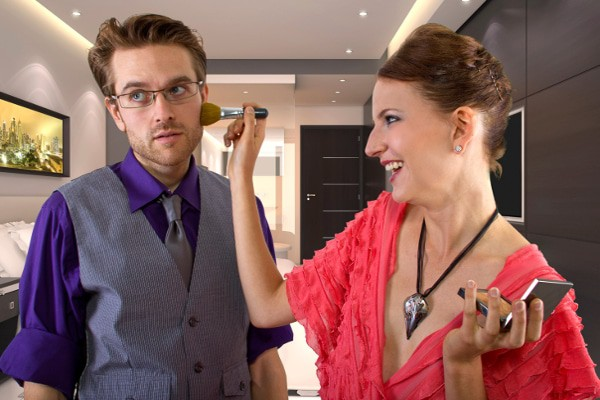 woman putting makeup on a man
