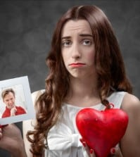 woman with broken heart and photo of ex boyfriend